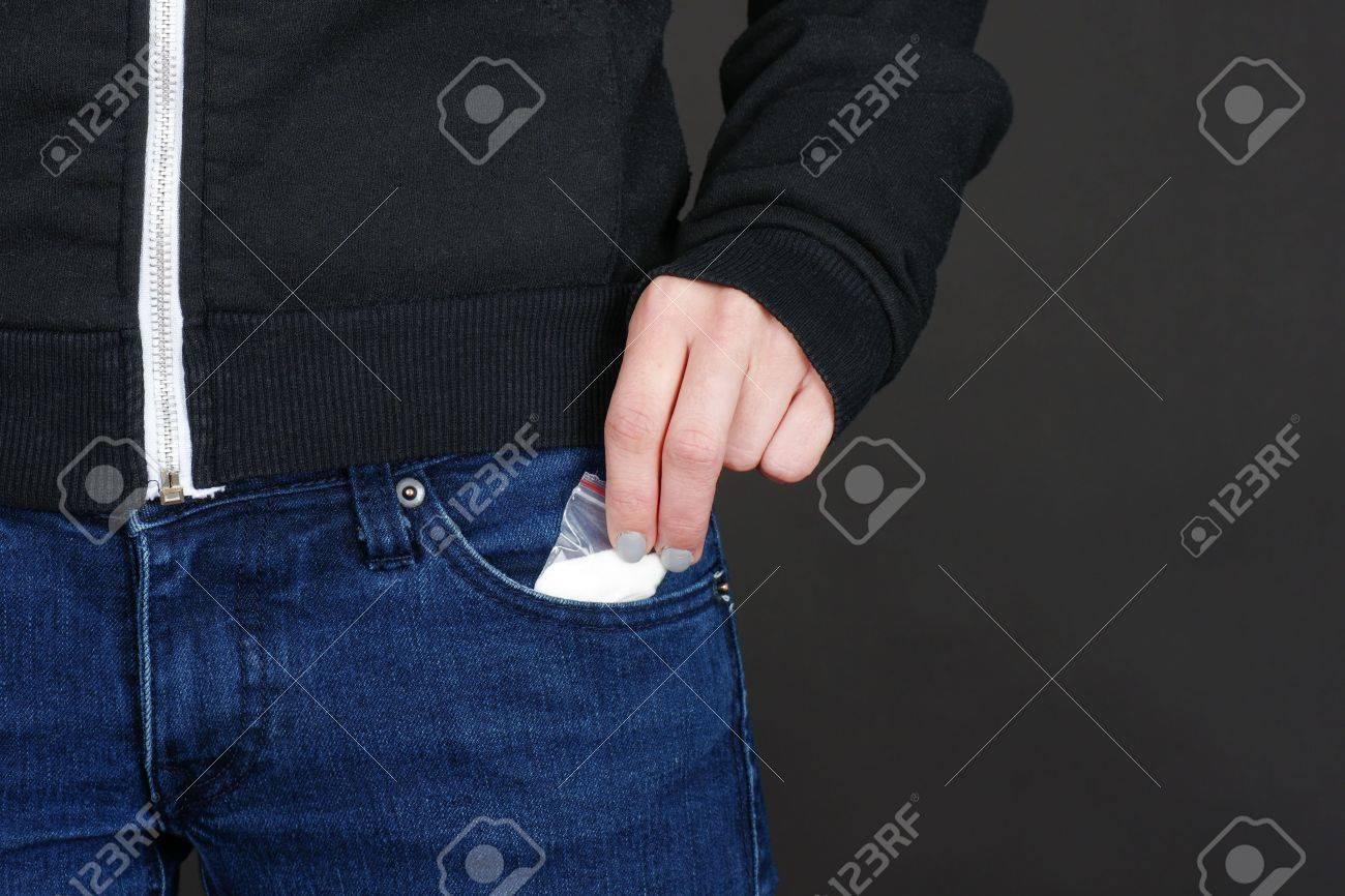 d3b655991 Foto de archivo - Mano femenina recuperación de nuestro paquete de la droga  de su bolsillo de jean azul con copia espacio en negro.