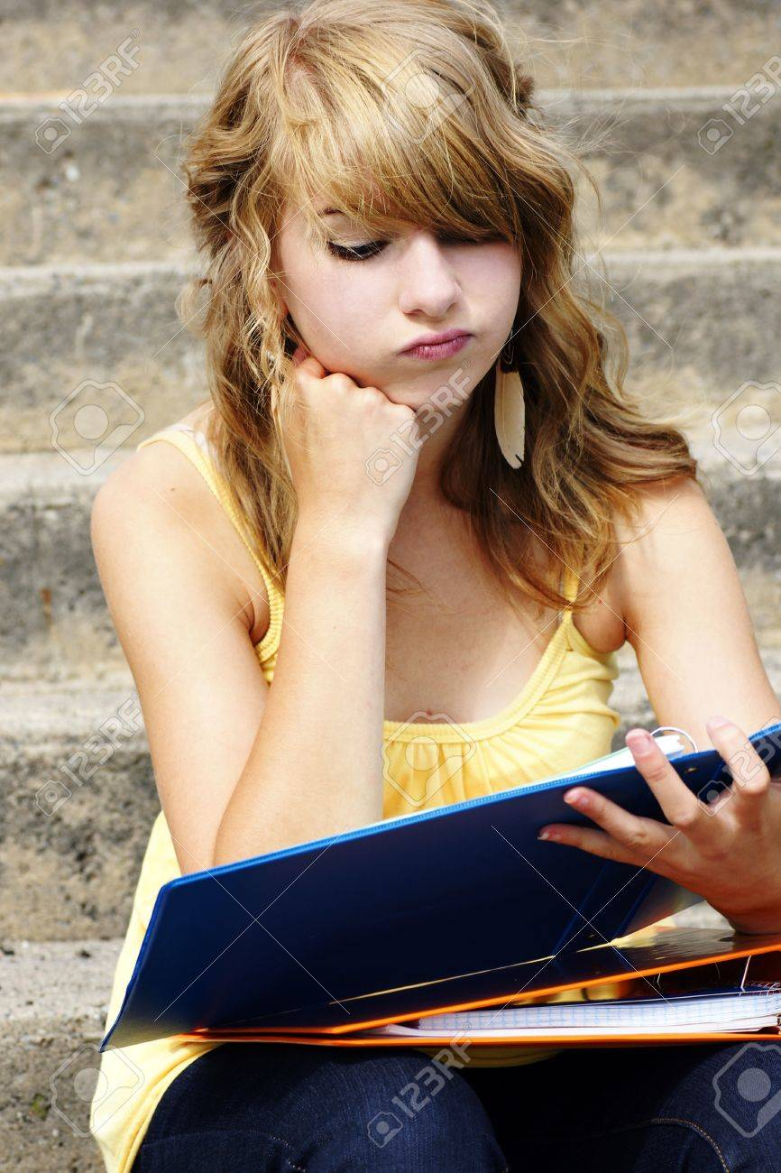 516b5bf1d90 Stock Photo - Unhappy or frustrated young blond teenager girl going back to  school or looking at her homework in a binder.