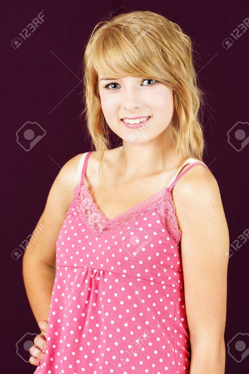 Portrait Of Cute And Innocent Yound Blond Teenager Girl Smiling Studio Shot Over Deep Pink