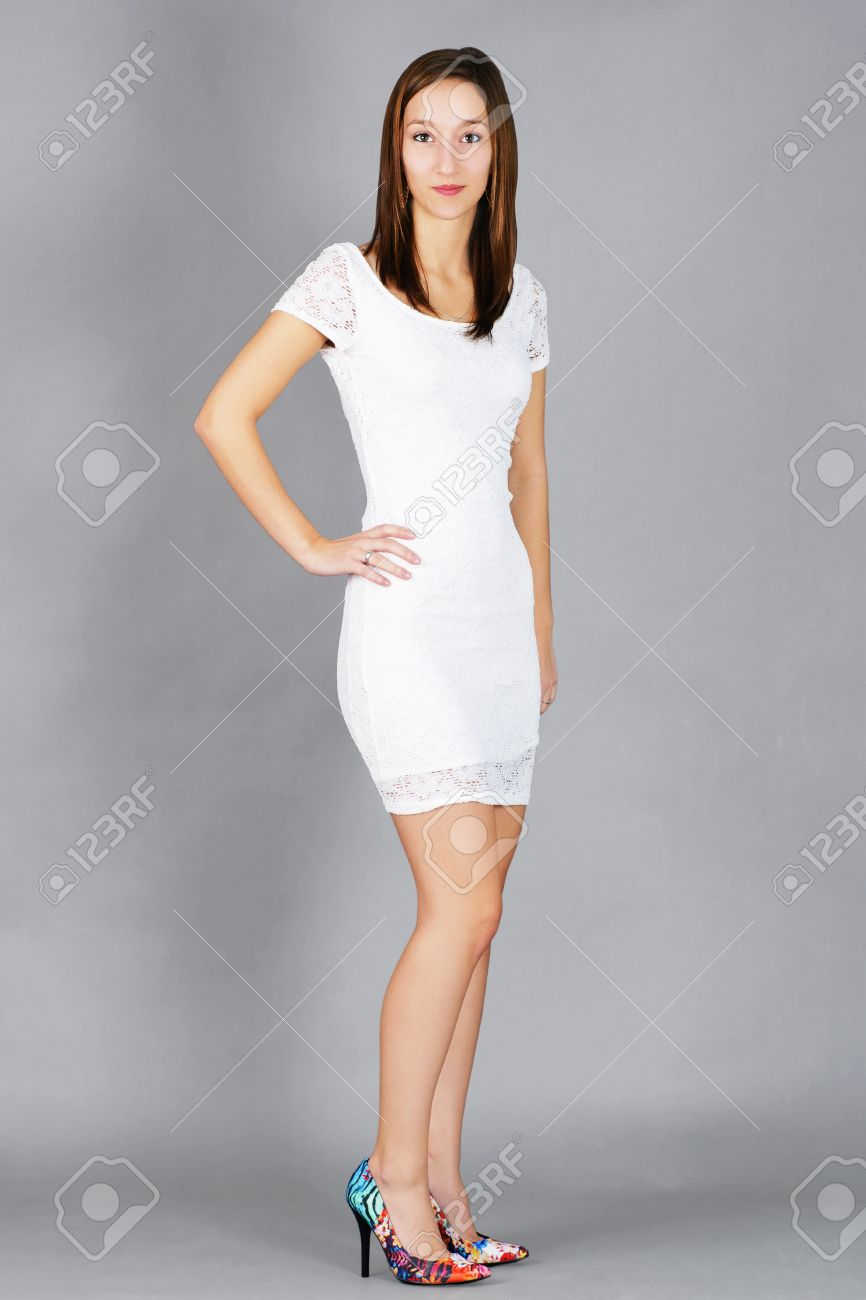 59f57af2a8 Foto de archivo - Joven y bella mujer morena con vestido de encaje blanco  con coloridos zapatos de tacón alto listos para salir