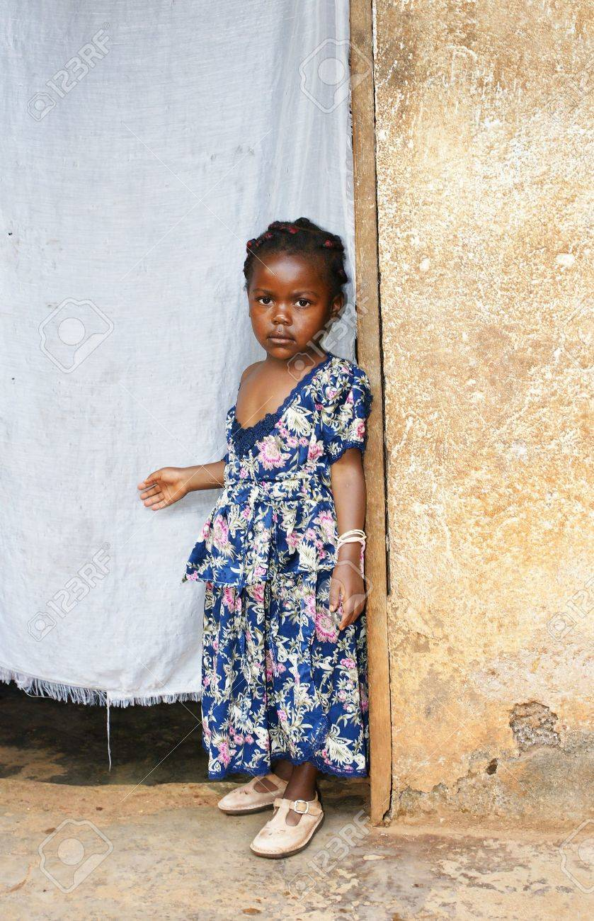 Cute but serious little black African girl in pink sunday dress next to her home door made of fabric; third world or developing country concept. - 17742476