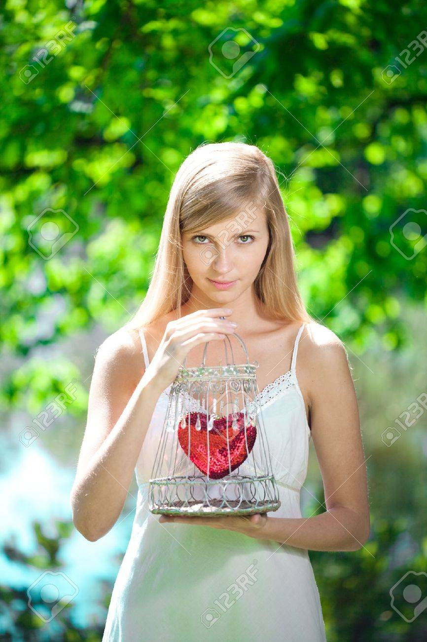 Beautiful sad woman with a heart in a cage Stock Photo - 14644861