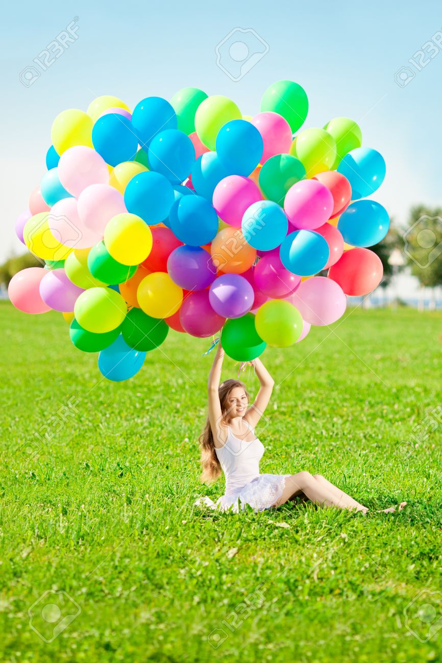 Happy Birthday Woman Against The Sky With Rainbow Colored Air Balloons In Her Hands