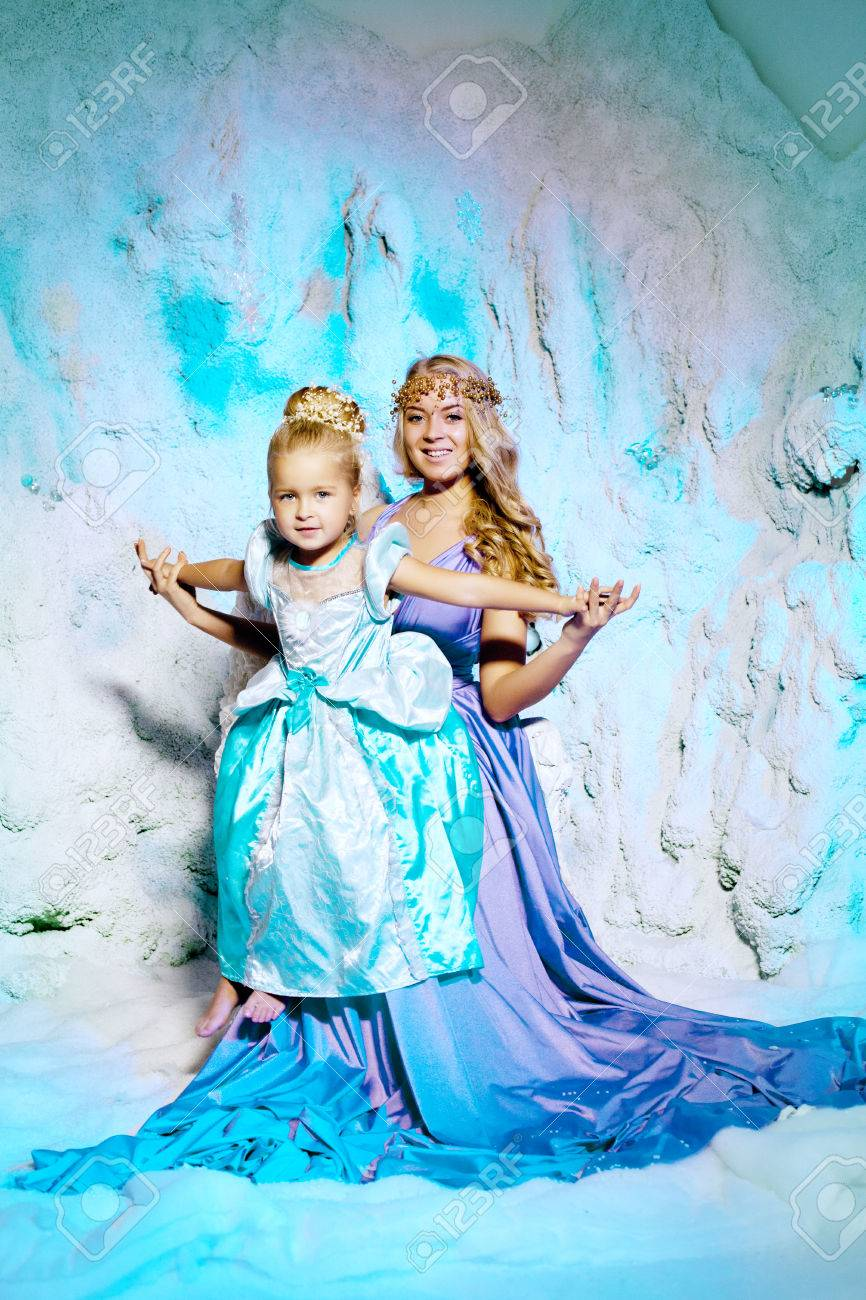 9f5b8da311146 Little girl with mother in princess dress on a background of a winter fairy  tale. Baby and mom snow queen. Sweet smiling child and mum snowy kingdom.