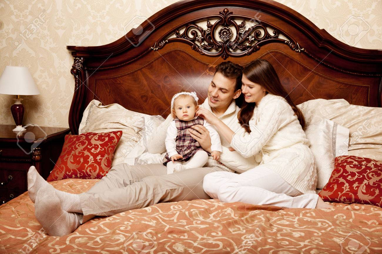 Stock Photo   Young Family In The Bedroom. Mother, Father And Daughter In  The Interior. Mom, Dad And Baby Are Playing Together.