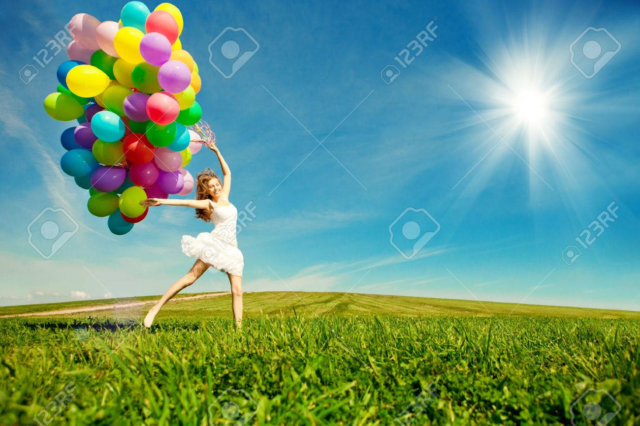 Happy birthday woman against the sky with rainbow-colored air balloons in hands. sunny and positive energy of nature. Young beautiful girl on the grass in the park. - 30697087
