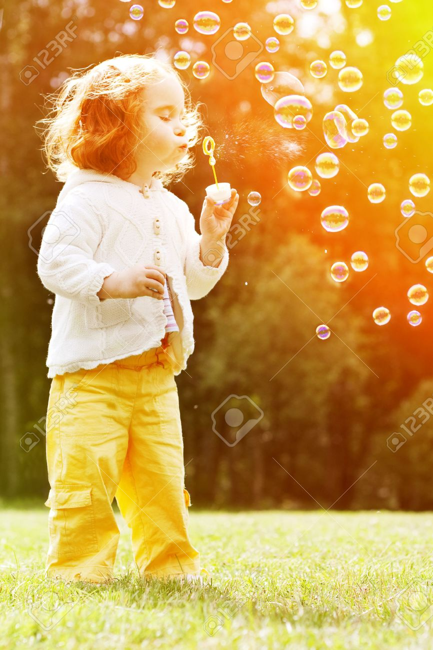 Child blowing a soap bubbles. Kid blowing bubbles on nature. Baby at sunset, the sun's rays - 31224855