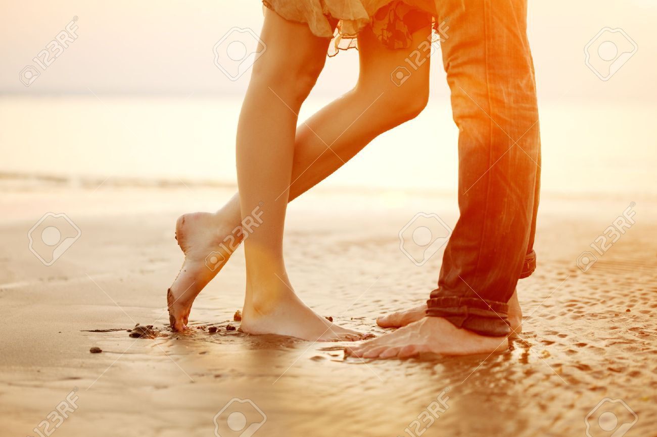 A young  loving  couple hugging and kissing on the beach at sunset. Two lovers, man and woman barefoot near the water. Summer in love Stock Photo - 39395526