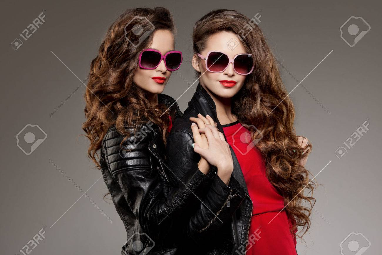 Sisters twins in hipster sun glasses laughing Two fashion models Women smiling positive Friends group having fun, talking Youthful friendship youth adults people culture concept Young girls rock party - 39395662