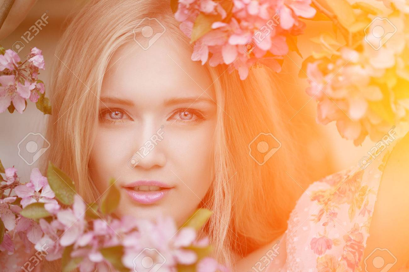 Young spring fashion woman in spring garden. Springtime. Trendy girl at sunset in spring landscape background. Allergic to pollen of flowers. Spring allergy - 39395823