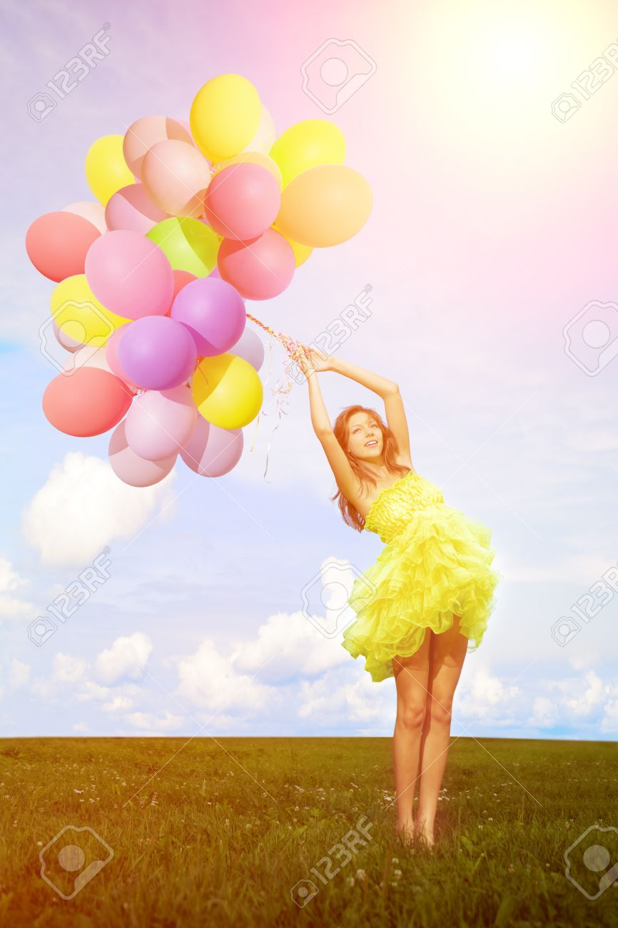Happy Birthday Woman Against The Sky With Rainbow Colored Air Balloons In Hands Stock
