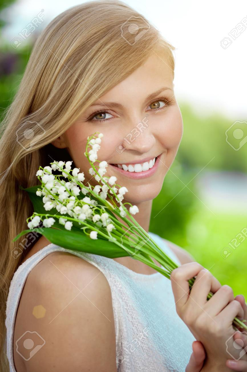 Young woman with a beautiful smile with healthy teeth with flowers. - 58593161