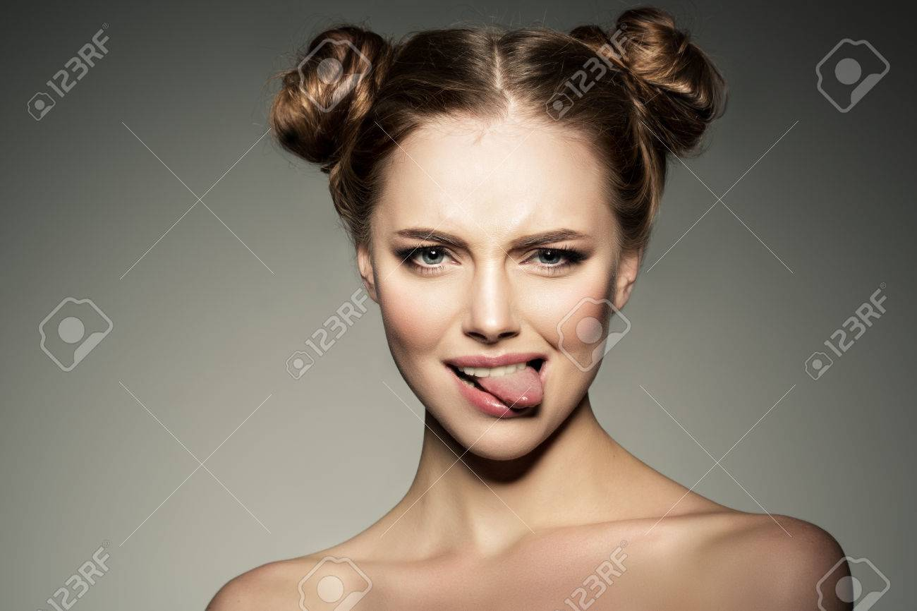 Emotional girl. Beautiful modern model shows tongue Positive woman hipster. Emotions on face. - 67198530