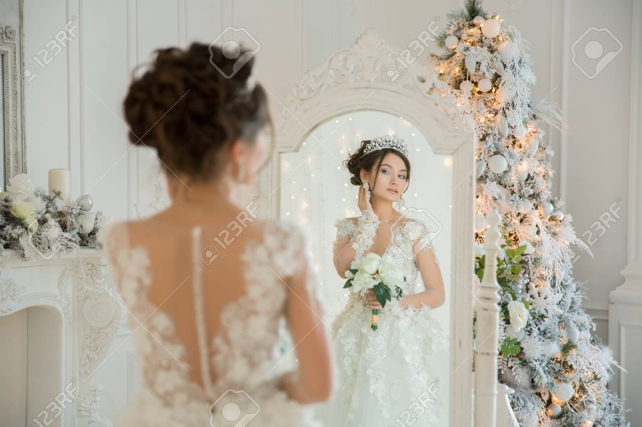Beautiful Bride In A Wedding Dress At A Mirror In Christmas... Stock ...