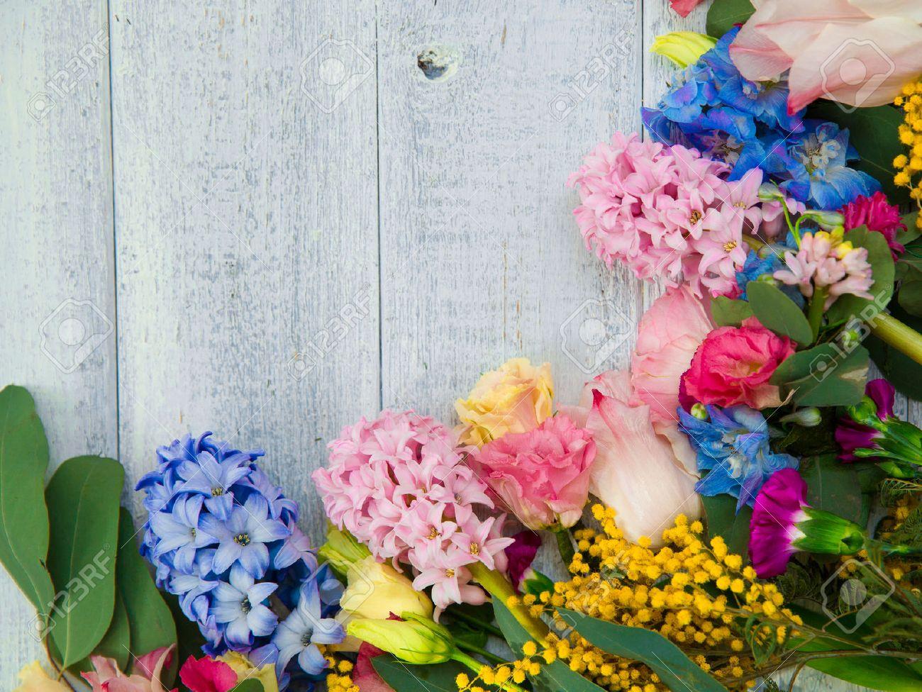 Spring flowers on wood background summer blooming border on stock spring flowers on wood background summer blooming border on a wooden table stock photo mightylinksfo Gallery