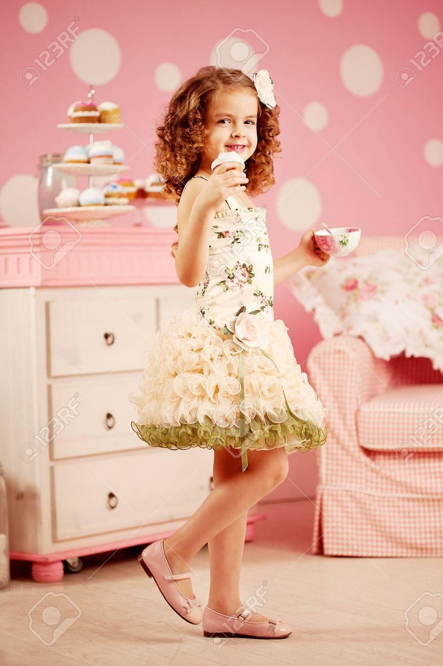 Kleines Nettes Mädchen In Einem Rosa Kleid Trinkt Tee Mit ...