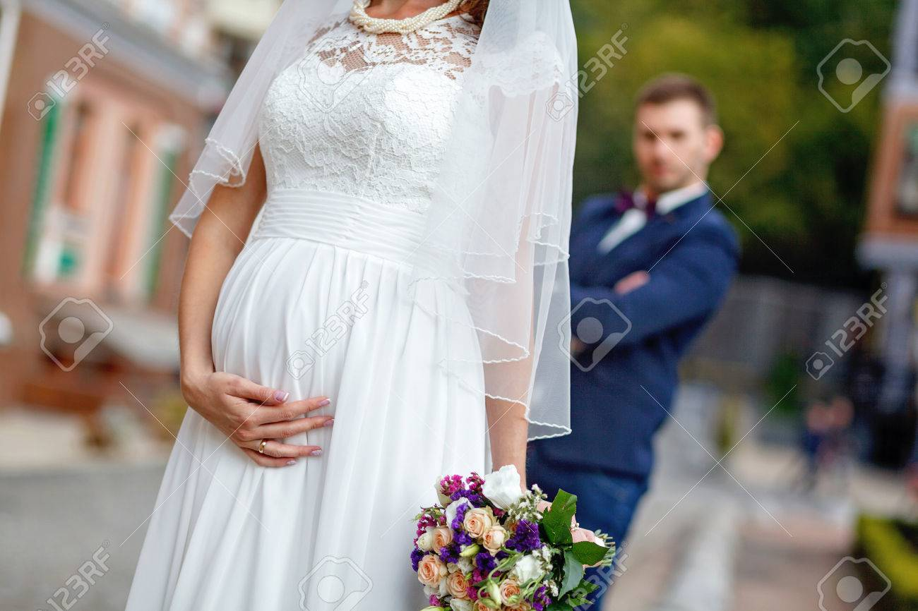 bc2e77cdb23c8 Pregnant bride in a wedding gown holding belly with hands. the groom in a  tuxedo