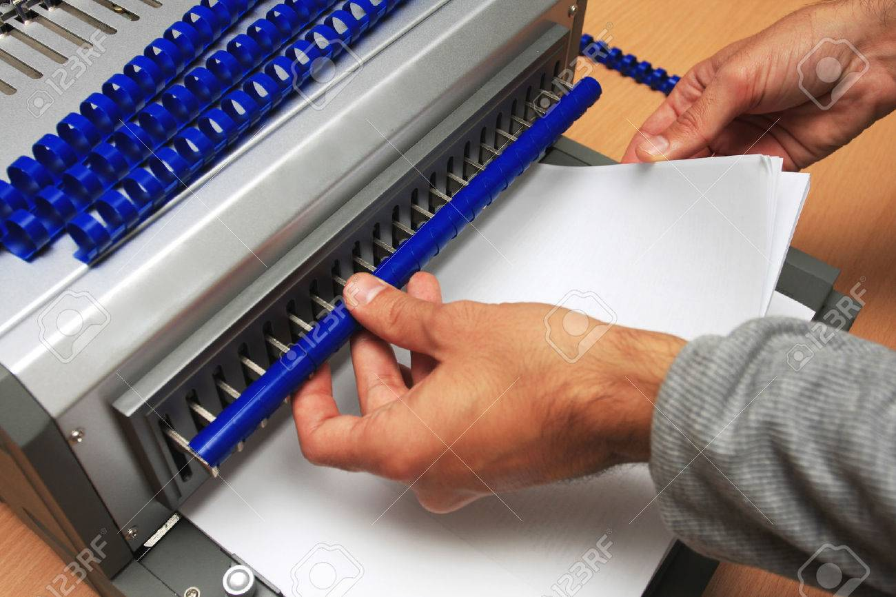 Gray Binding machine with man who works on it - 52366421