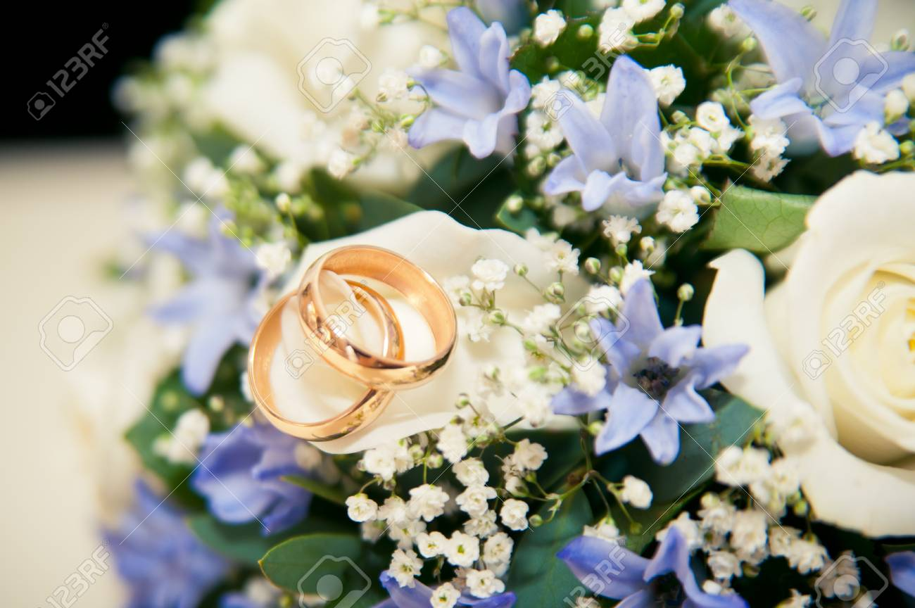 Wedding rings lie on a bouquet of blue and white flowers stock photo stock photo wedding rings lie on a bouquet of blue and white flowers izmirmasajfo