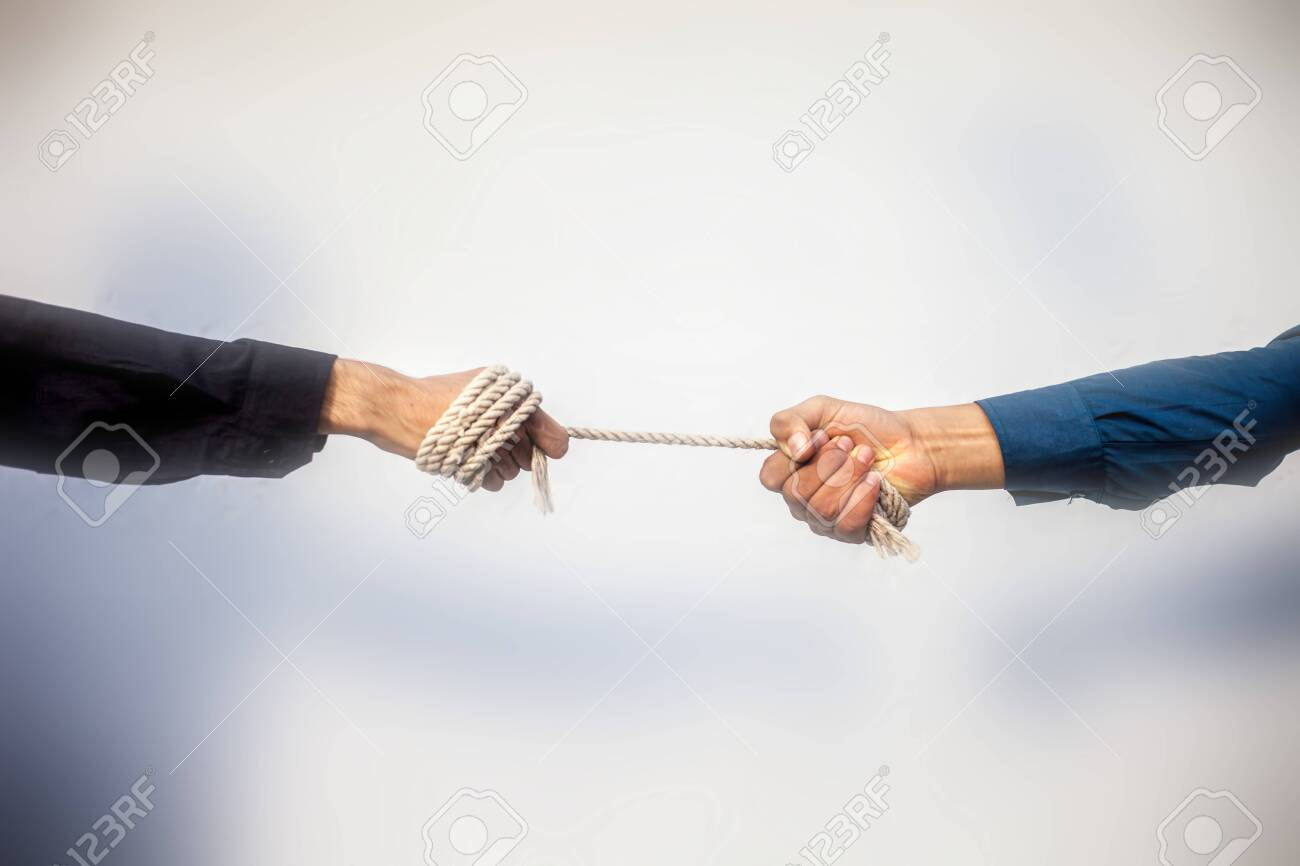 Close up shot of two male hand playing tug of war over blurred background. - 146183717