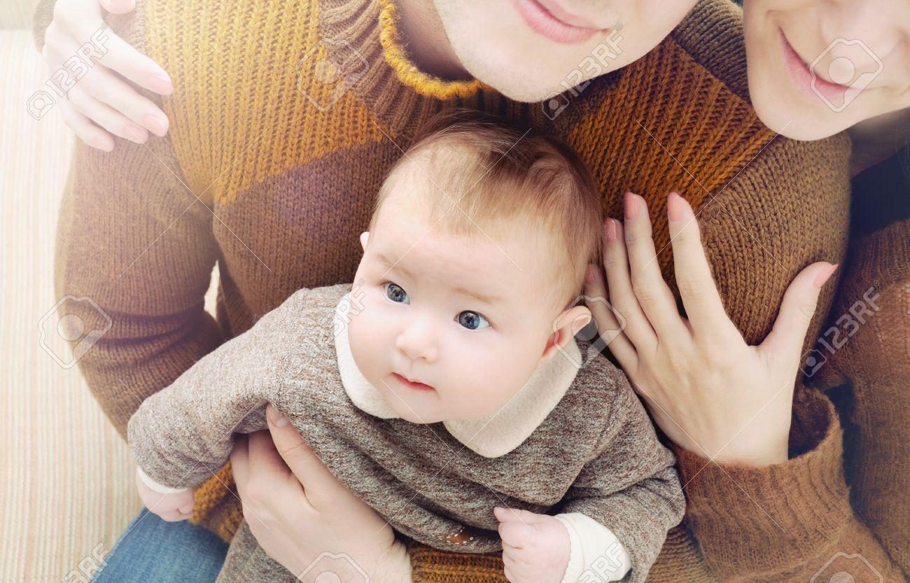 Banque dimages famille heureuse de trois petit bébé mignon avec de grands yeux assis sur le parent