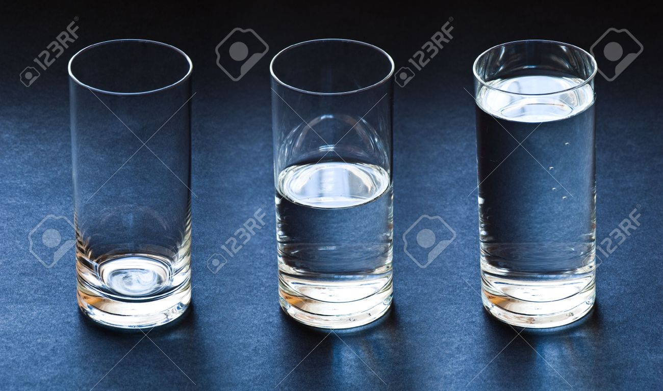 three glasses empty half and full with water on dark blue background - 13319195