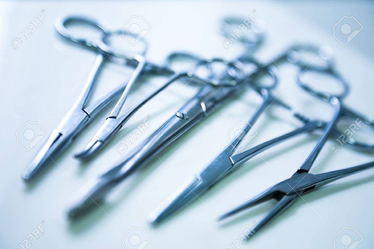 medical clamp instruments on table with shallow depth of field - 13320205