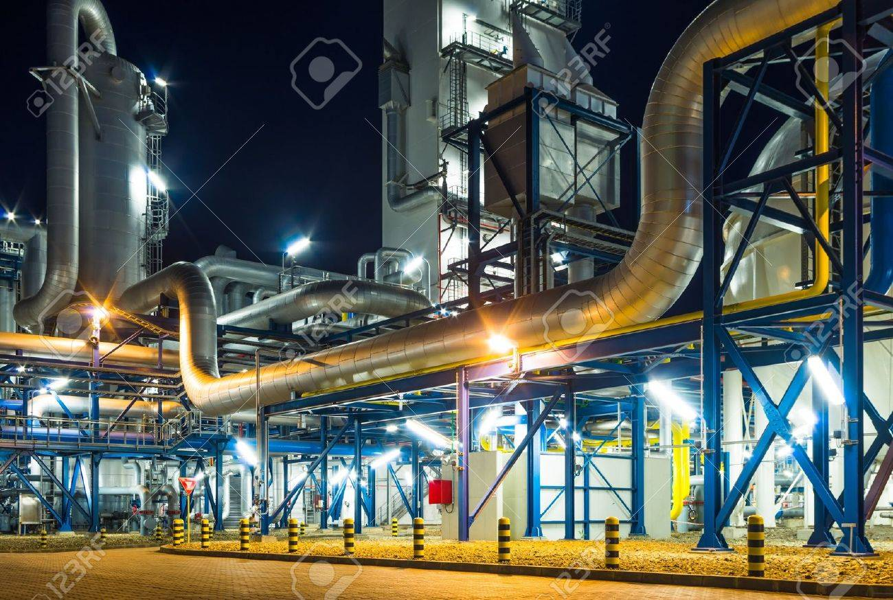 pumps and piping system inside of industrial plant at night - 19942555