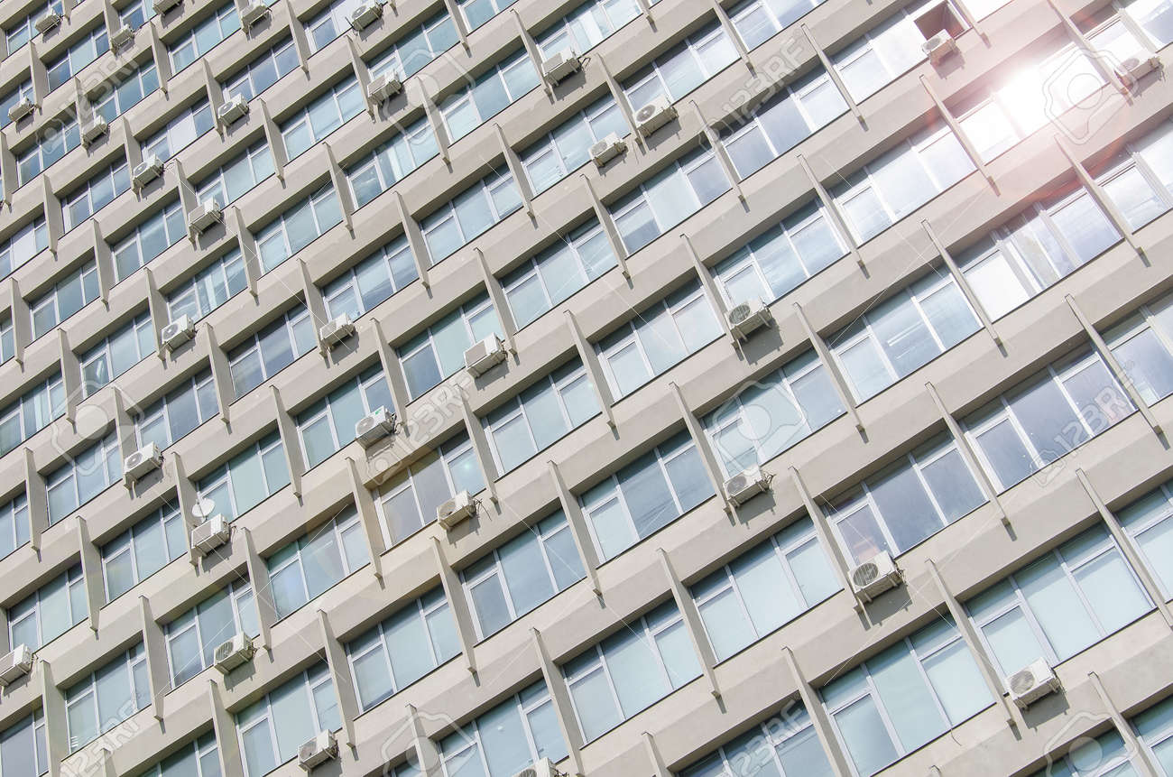 The texture of the facade of a soviet building with a lot of windows and air conditioners - 170794893
