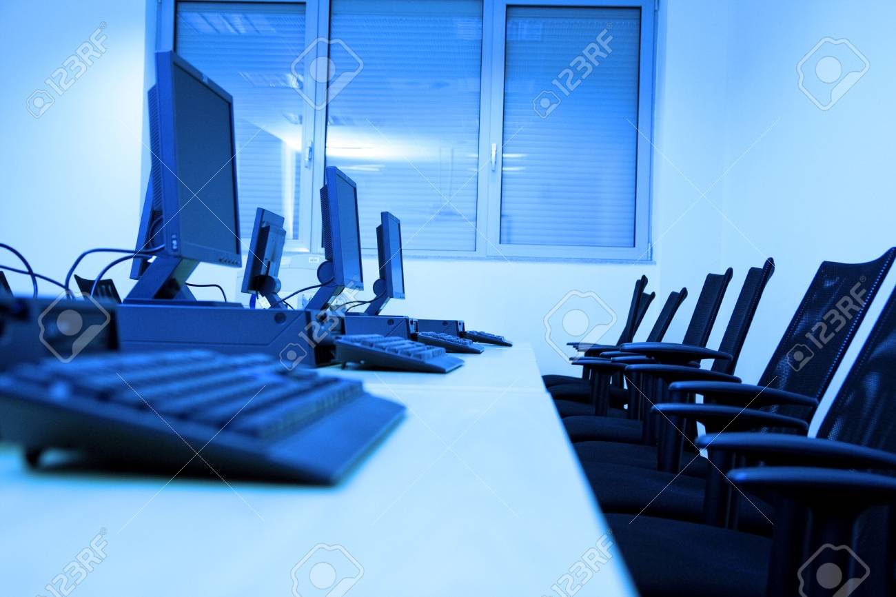 Room equipped with black computers. Image has blue tint. Stock Photo - 4623972
