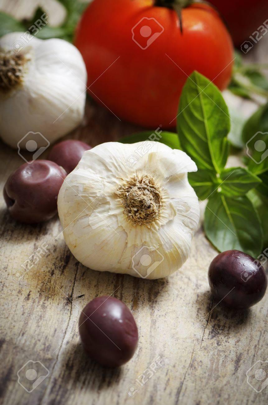 Food ingredinets. Garlic, olives, tomato and basil on wooden table. - 21724821