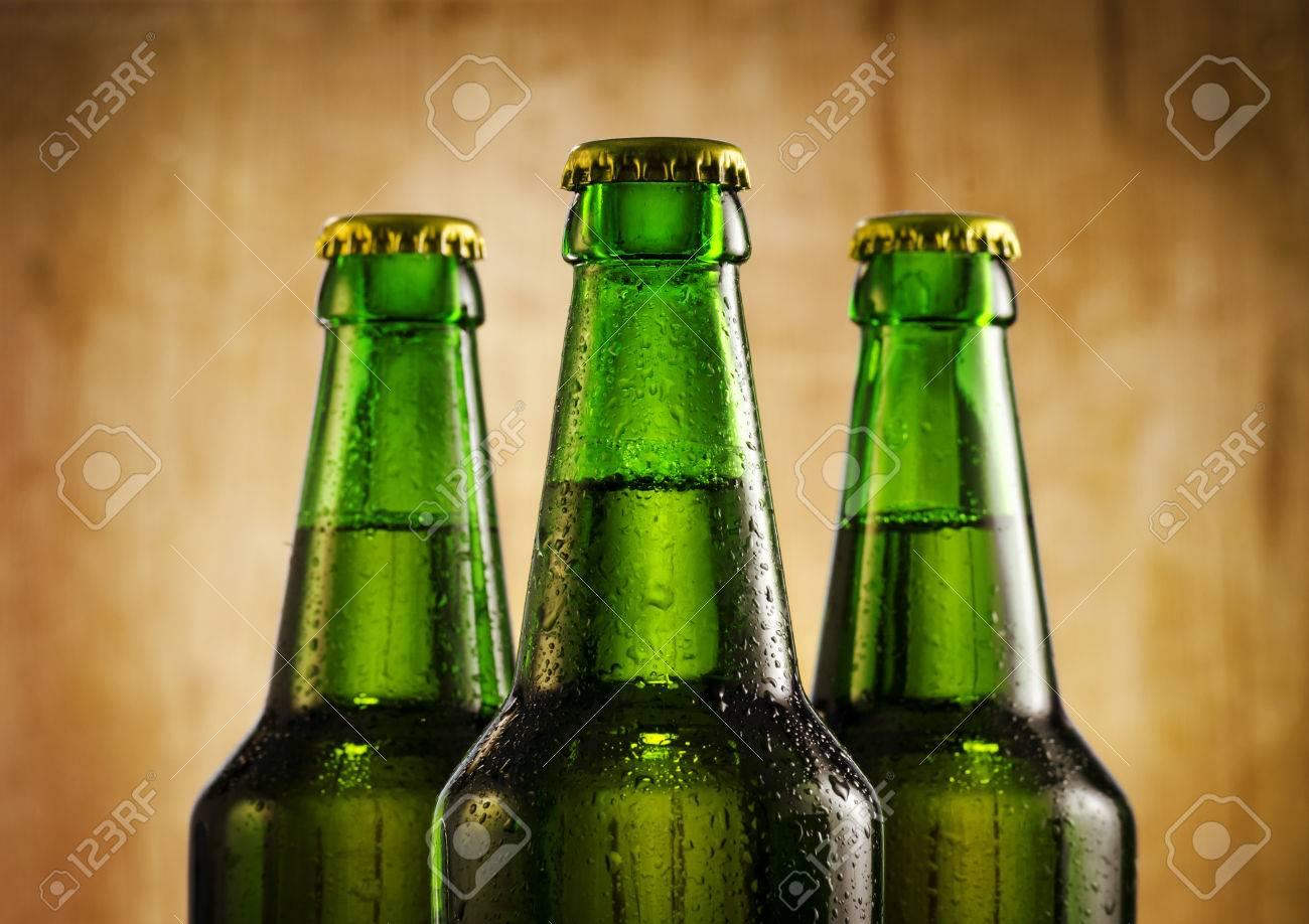 Wet beer bottles on rustic wooden background - 25309732