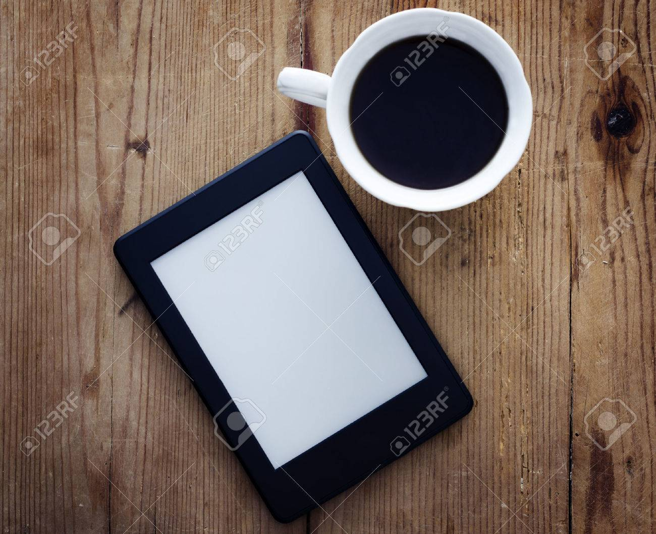 E-book reader and coffee cup on wooden table - 27742055