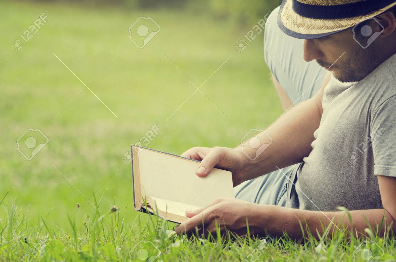 Man reading a book on the grass - 30749104