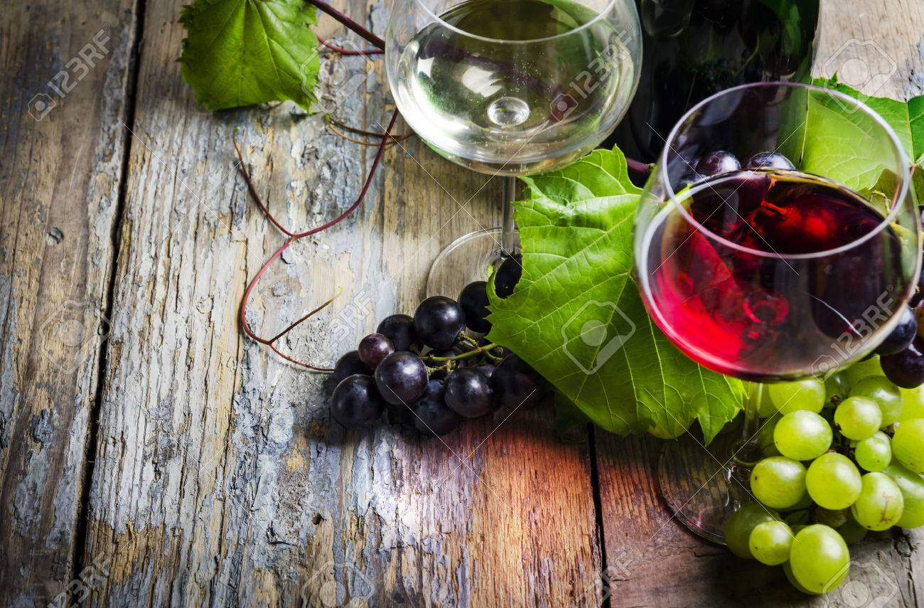 Wine glasses and grape on rustic wooden table - 31528318