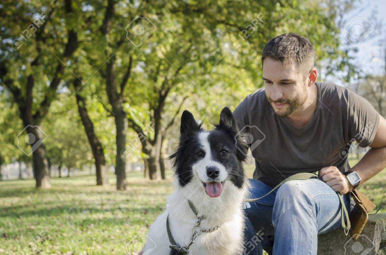 Man with his dog playing in the park - 33988746
