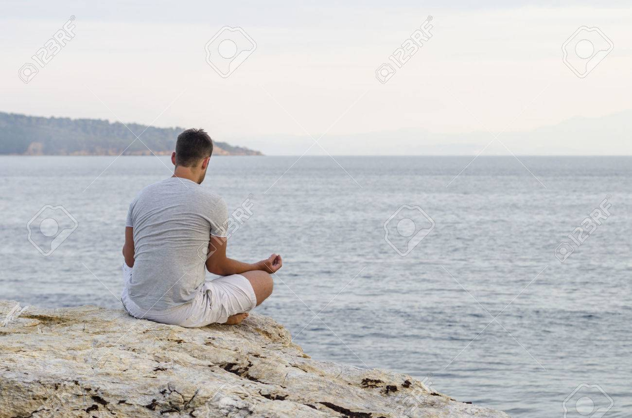 Young man sitting on the coast and meditating - 42082519
