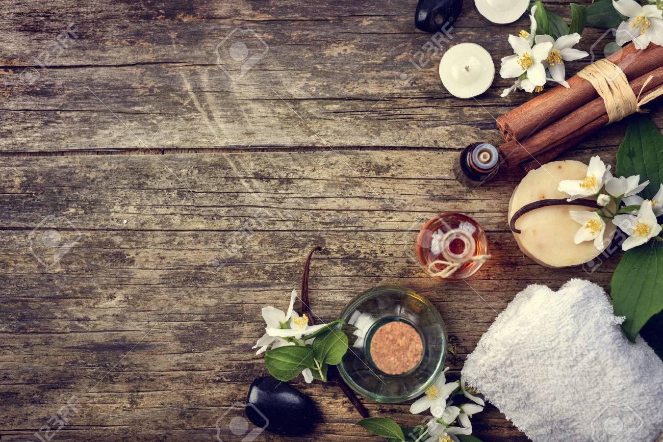 Essential oils with jasmine, cinnamon and vanilla on rustic wooden table, retor style image. - 57827638
