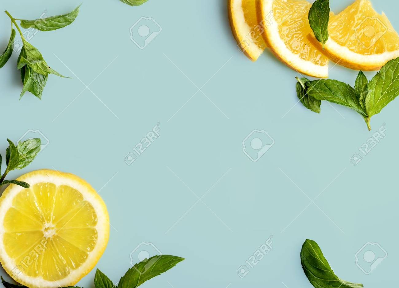 Citrus slices and mint herbs frame on retro mint background with copyspace - 64143397