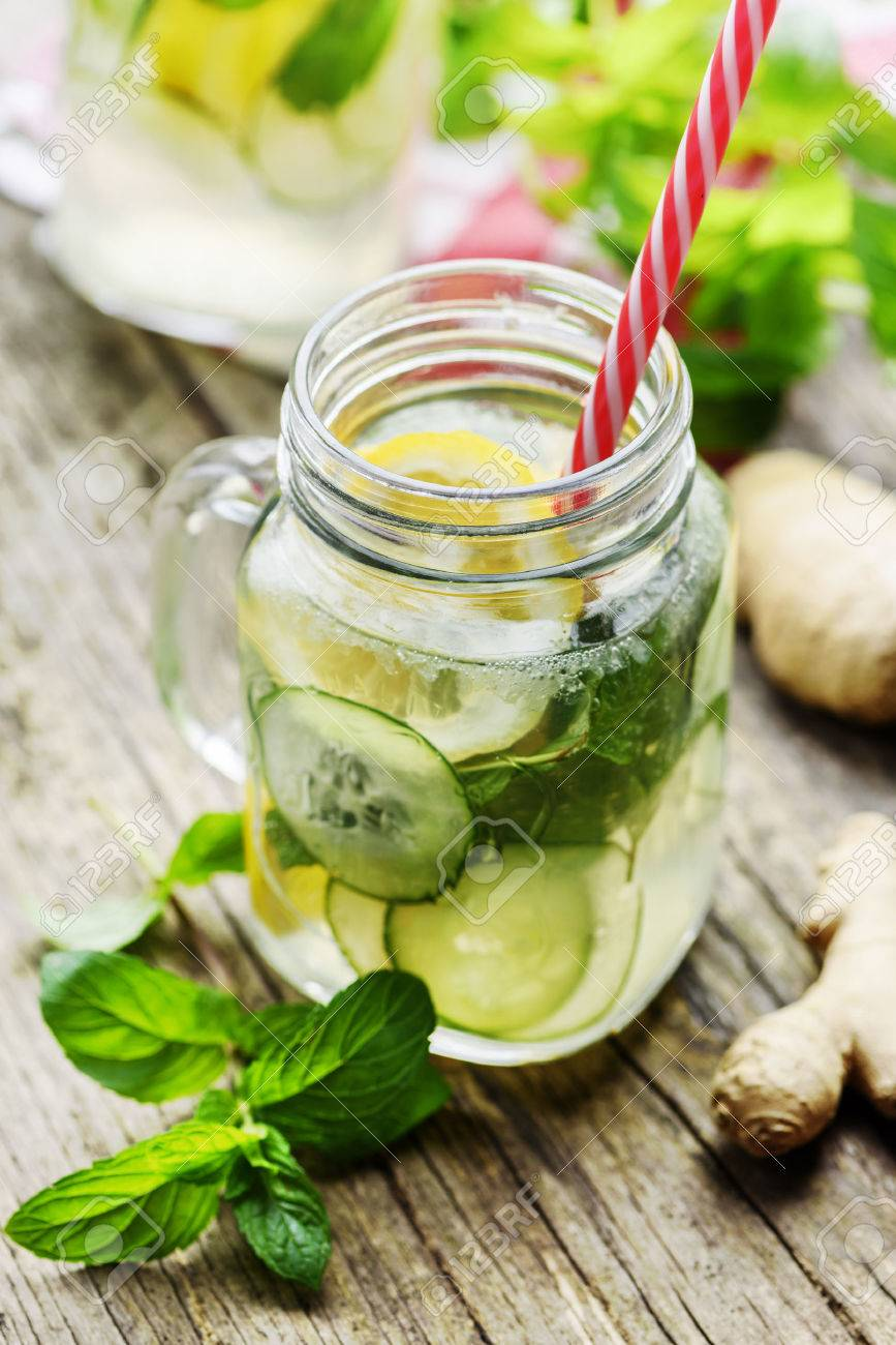 Detox drink with water, cucumber, lemonade and mint in mason jar glass with retro straws. - 65114163