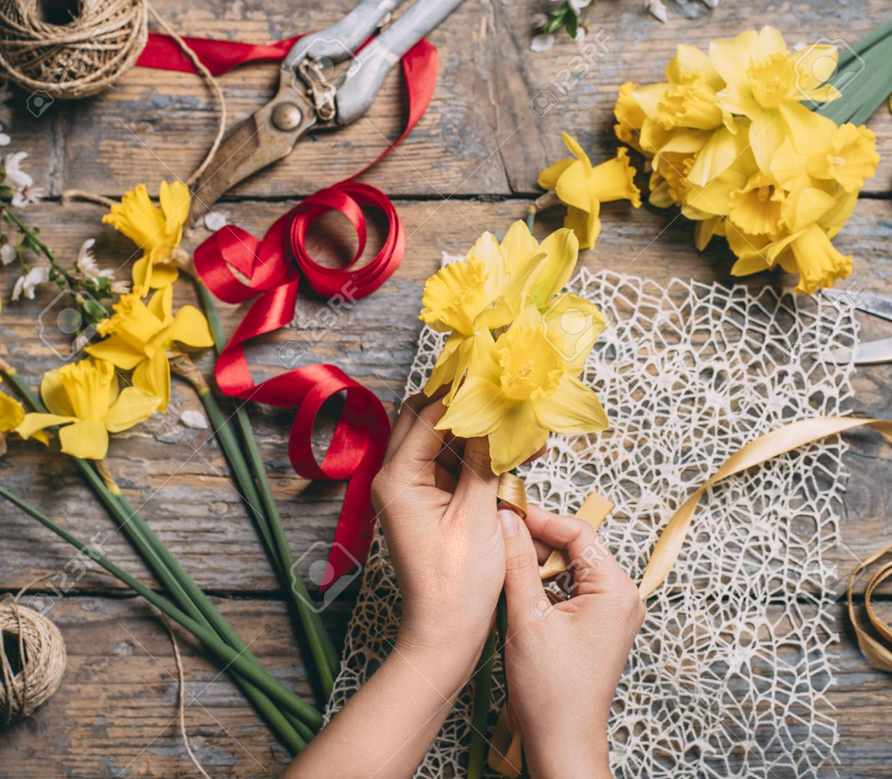Top View Of Florist Hands Making Flower Bouquet With Narcissus