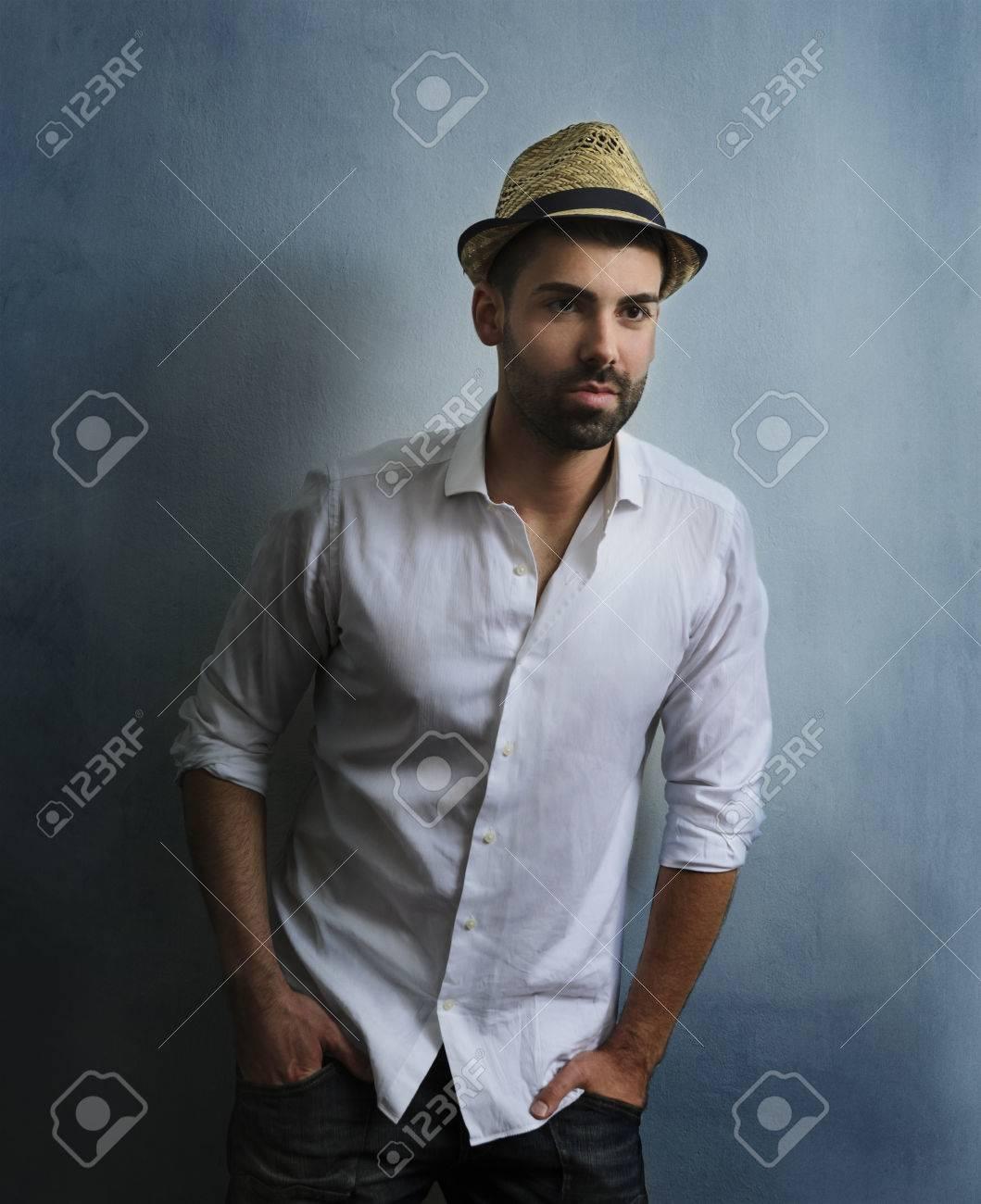 2031fa9ba316f4 Junge sexy Hipster Kerl mit Bart posiert vor der blauen Grunge Wand.  Porträt von stilvollen