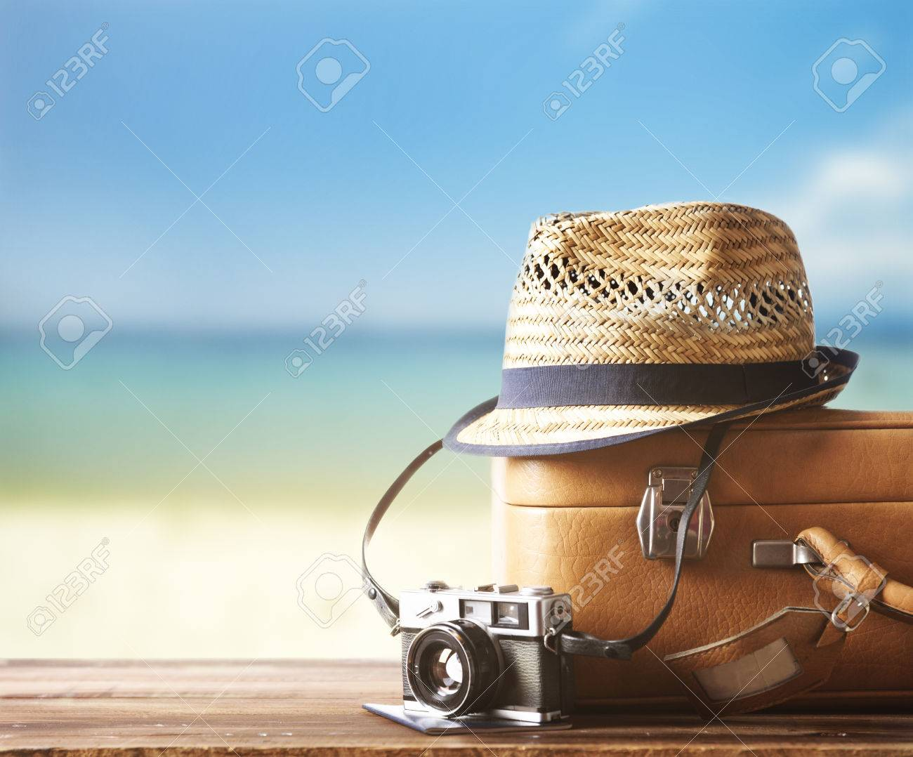 Vintage suitcase, hipster hat, photo camera and passport on wooden deck. Tropical sea and sandy beach a in background. Summer holiday traveling design concept. - 82160169
