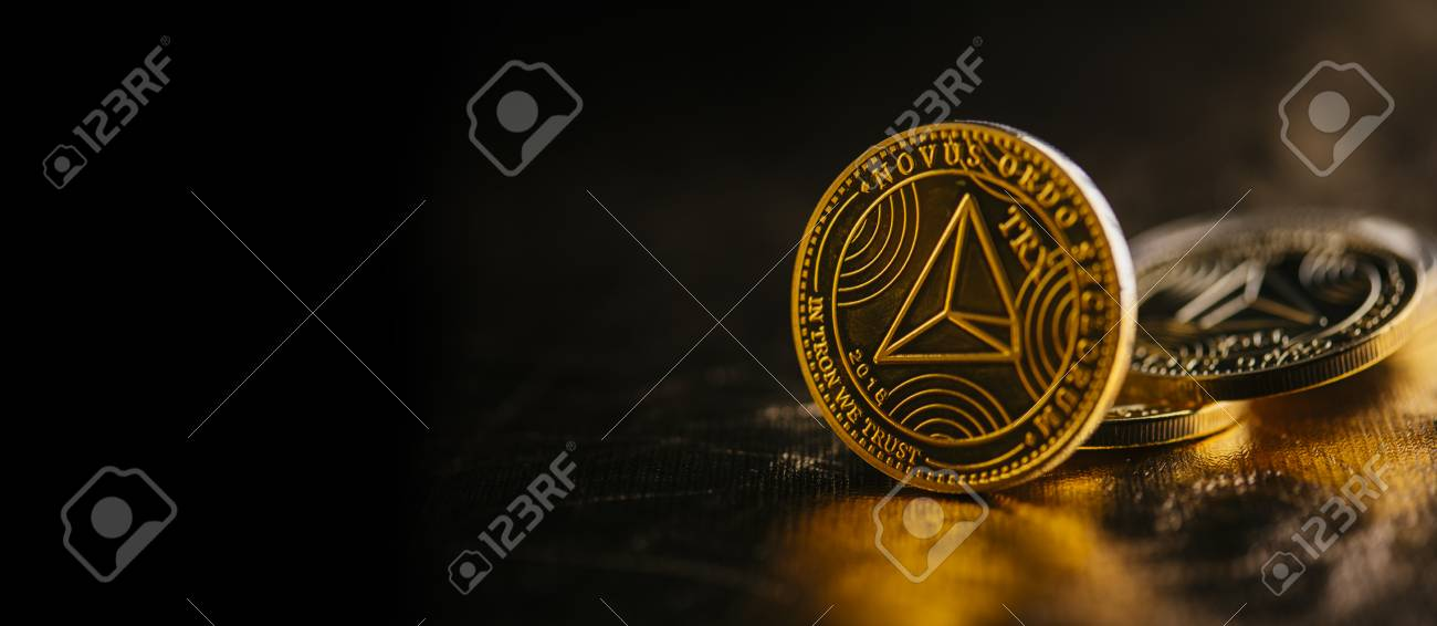 Closeup of golden tron coin cryptocurrency over black and gold