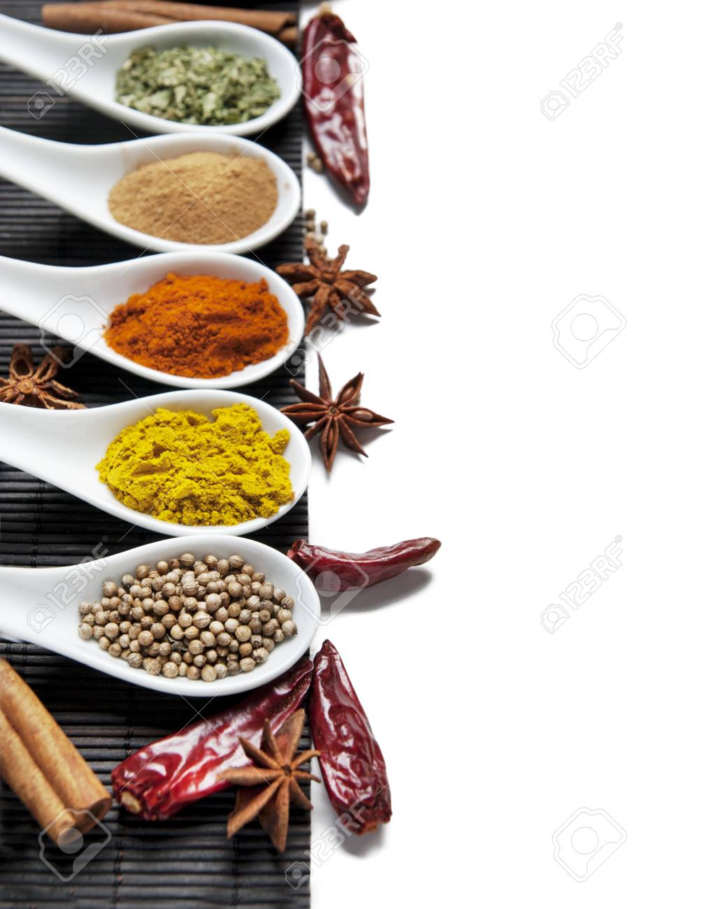 Top view on mixed dry colorful spices in spoons isolated on white background. Indian food and oriental cooking ingredients. Asian restaurant food menu design. Curry, chili, paprika, pepper, cinnamon. - 114900786