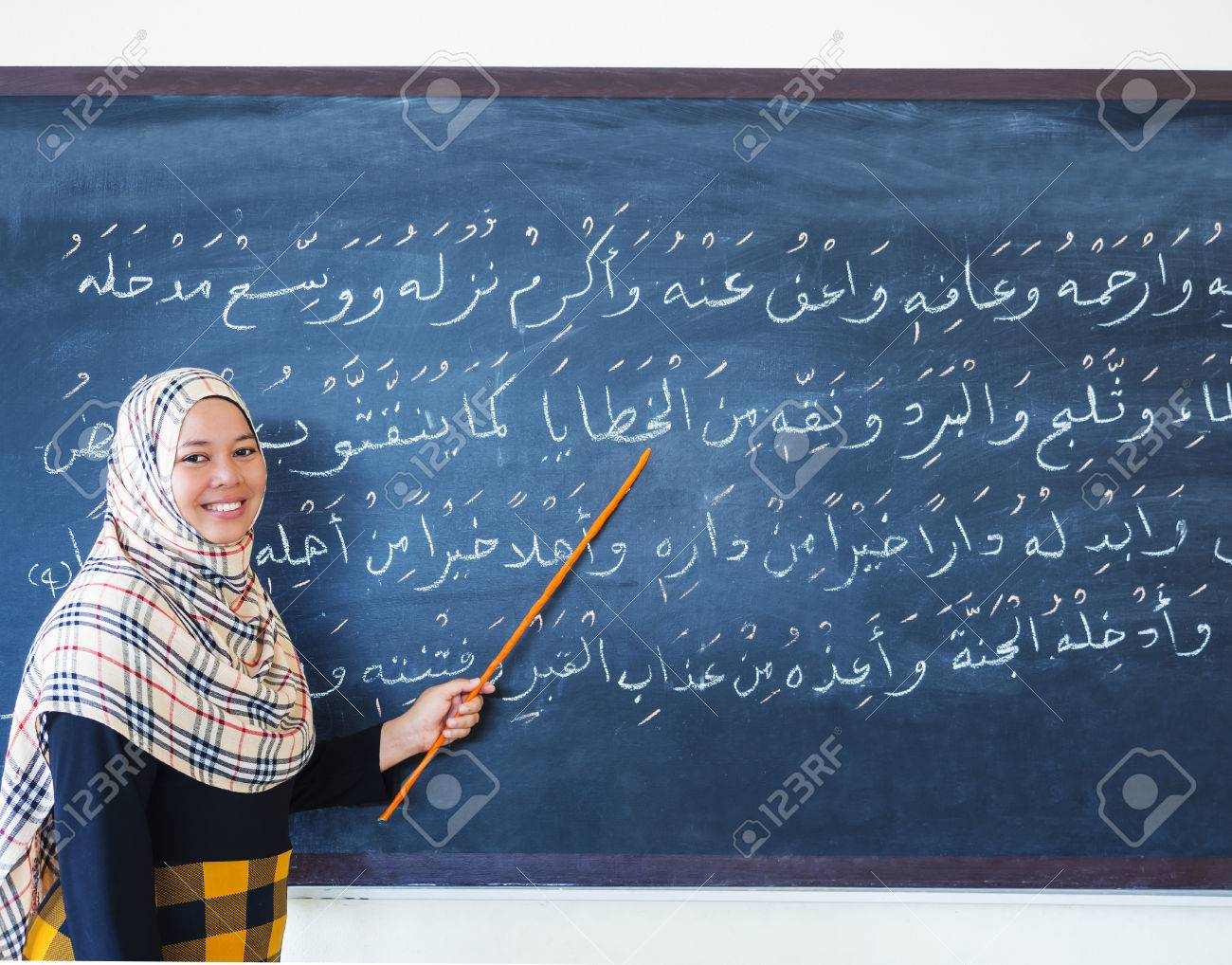 muslim woman teaching islamic the prayers in arabic on chalkboard