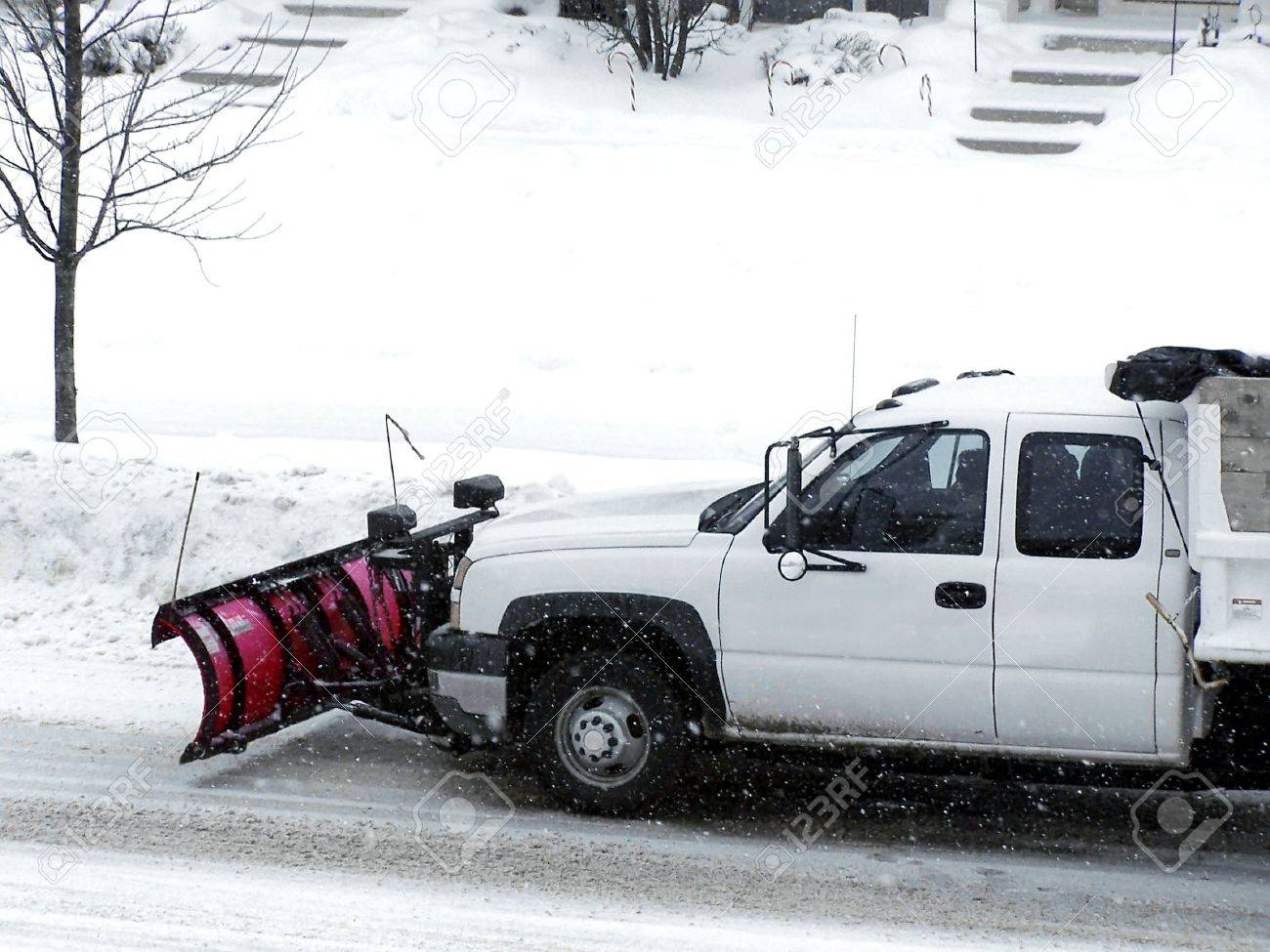 Stock image of a white truck with a red plow clearing the snow Stock Photo - 3671495