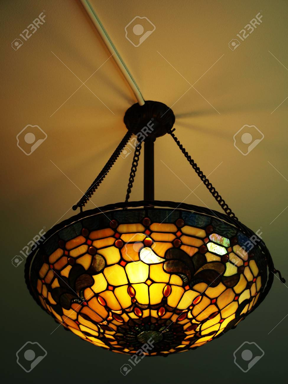 Photo of a beautiful lit tiffany style ceiling lamp in warm and