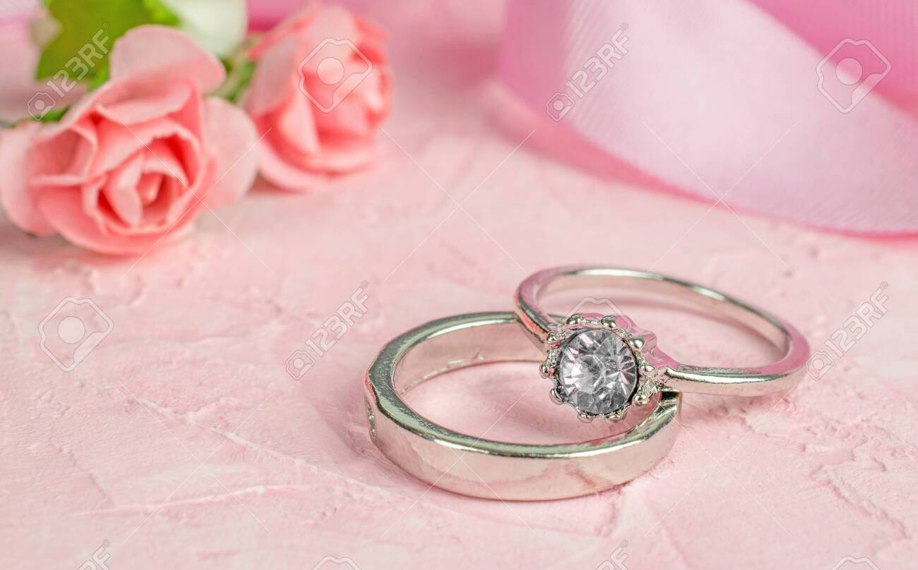 A Pair Of Silver Wedding Rings On A Pink Textured Surface With