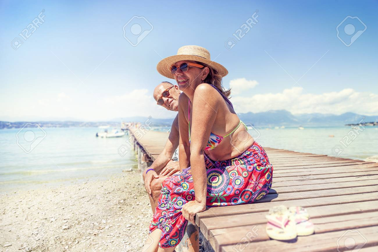 Portrait of modern mature couple relaxing in swimsuit sitting